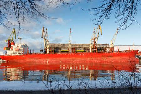 A big cargo ship reflecting on a river