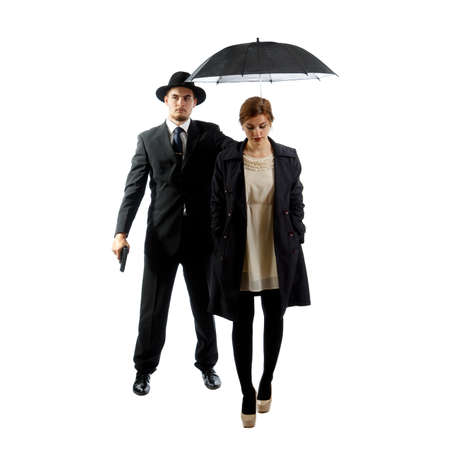 An elegant lady with a bodyguard holding a gun and a black umbrella Stock Photo