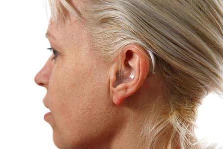 digital hearing aid in womans ear Stock Photo