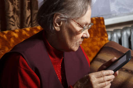 old woman using ebook reader