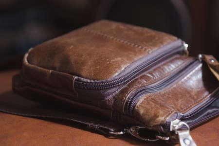 brown leather mens handbag lying on chair 스톡 콘텐츠