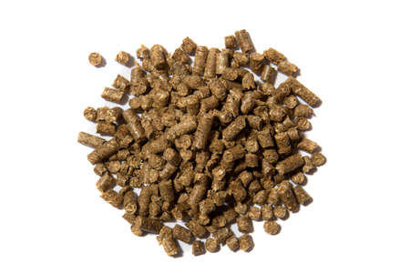 Light brown pressed solid wooden pellets granules on white background