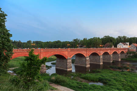 The old brick bridge over the Venta River in the evening. Kuldiga Latvia Stock Photo