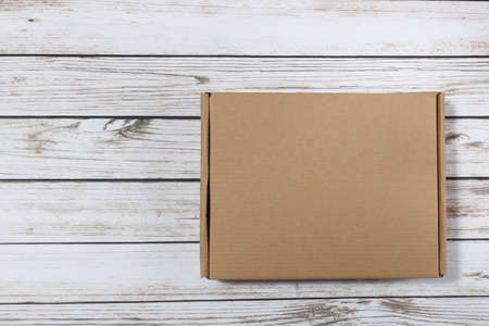 plain cardboard box on a wooden background Stock Photo