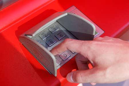 close up of hand entering pin code at cash machine