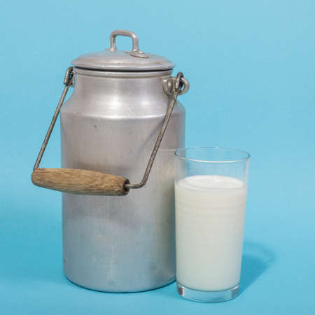 Glass of fresh milk and retro milk canister on blue background