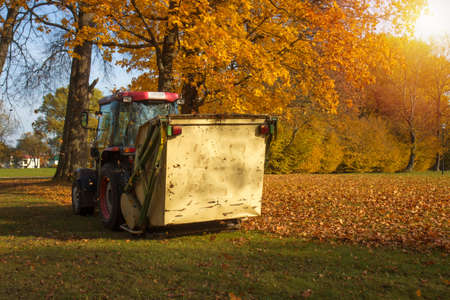 Vacuum sweeper towed by a tractor work in autumn park. Collect leafs.