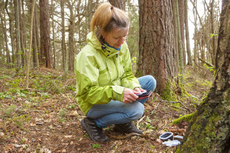 A woman geocaching. Women in woods find geocache container. Big ammo box with log book and some toys.