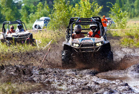 An ATV sprays mud as it zips around a corner in a dirt road rally