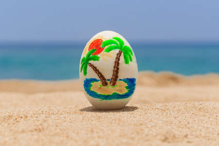 Easter egg, painted with tropical pattern on the ocean beach 写真素材