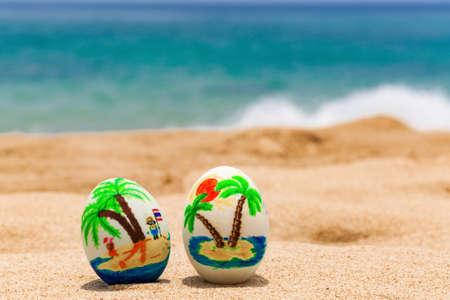 huevos de pascua: Huevos de Pascua pintados con las palmas en la playa del oc�ano Foto de archivo