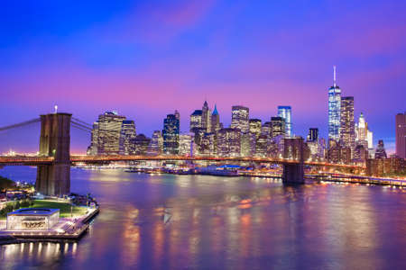 Night view of Brooklyn Bridge and Manhatten with reflection in water