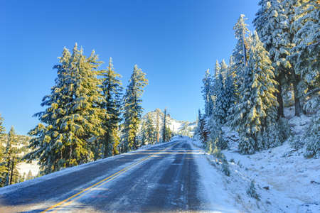 crater lake: Snowy and icy winter road in morning light. Road around Crater lake, Oregon