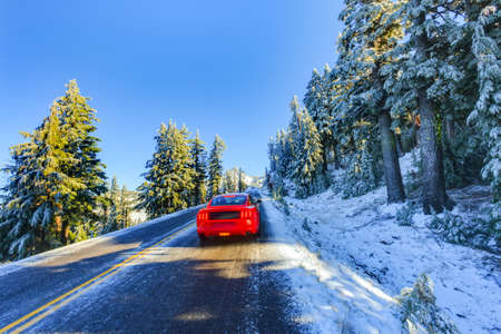 crater lake: Red car driving at snowy and icy winter road in morning light . Road around Crater lake, Oregon