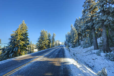 crater lake: Snowy and icy winter road in mornig light. Road around Crater lake, Oregon