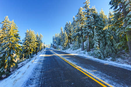 Snowy and icy winter road in morning light. Road around Crater lake, Oregon