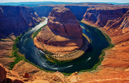 page arizona: Boat floating upstream at Horseshoe bend on the  Colorado river near Page, Arizona