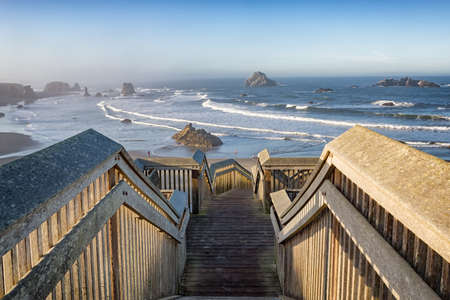 Wooden staircase leading to the coast Bandon Beach at sunrise, Oregon, USA