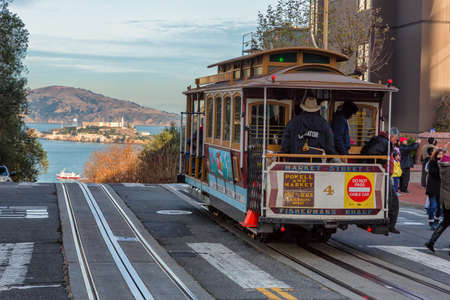 San Francisco, USA - December 22, 2017: city street view with a rail tram and Alcatraz prison island on background. Publikacyjne
