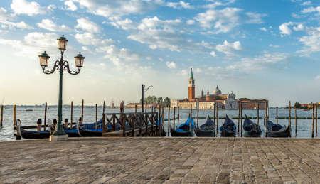 A row of gondolas parked beside the Riva degli Schiavoni in Venice, Italy. View of the Venetian Lagoon. The Church of San Giorgio Maggiore on island of the Venice, Italy, Europe