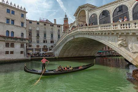 Venice, Italy - 12.06.2019: Gondola sailing on the Grand canal near to the Rialto bridge, Venice, Italy.