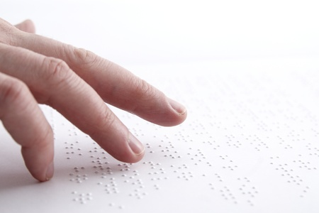sightless: Person reading braile in swedish.
