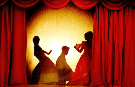 A man and woman in theatrical costumes in the theater of shadows on the stage with red curtains. Love in the shadows theater. Red curtain of opera, cinema or theater stage drapes.