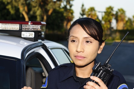 A Hispanic police officer with her radio.