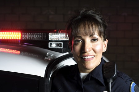 A Hispanic female officer standing in the night with her patrol car.  Stock Photo