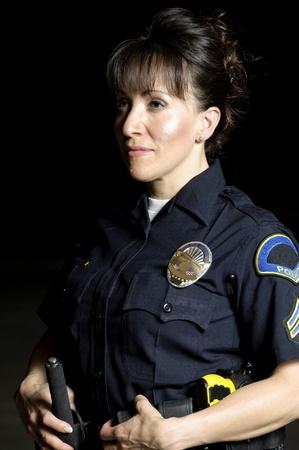 mujer policia: Un oficial de polic�a hispano mujer de pie en la noche.