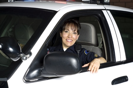 police badge: a female police officer sitting in her patrol car during a night shift.