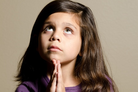 a little girl praying while she looks up.  Stock Photo - 11106804