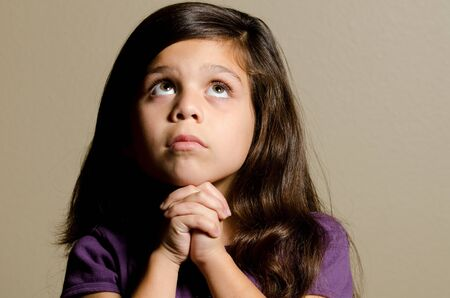 a little girl praying while she looks up.  Stock Photo - 11106802