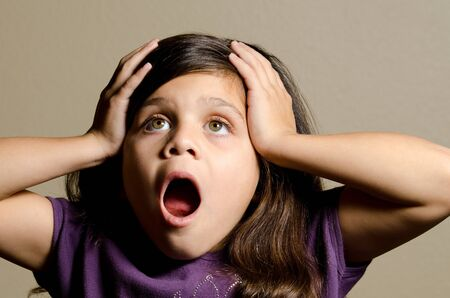 a little girl with her hands on her head in shock. Stock Photo