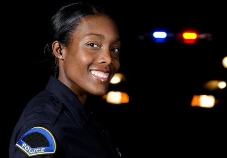 lightbar: A female police officer in the night during her shift with her patrol car in the background.  Editorial