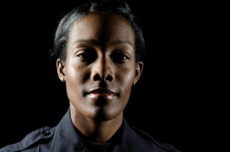 police badge: A female police officer in the night during her shift.