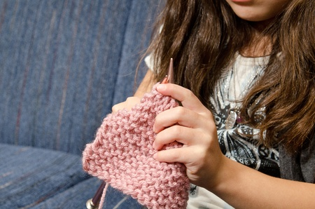 knitting: a little girl sits on the couch as she knitts.  Stock Photo