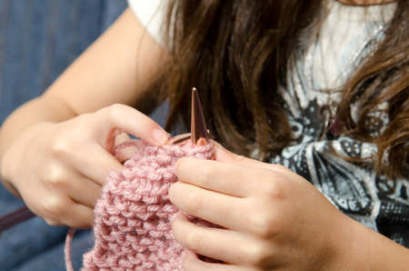 a little girl sits on the couch as she knitts.  Stock Photo - 12035760