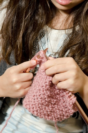 a little girl sits on the couch as she knitts.  Stok Fotoğraf