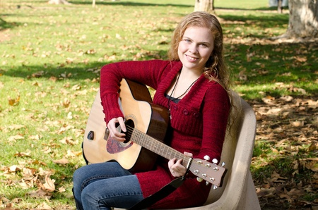 17 year old: a 17 year old teen playing her guitar in the park.