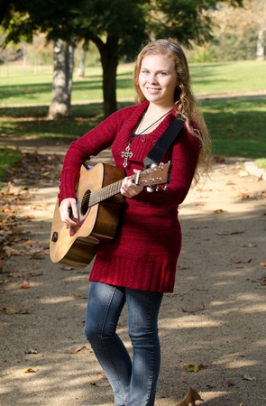 16 17: a 17 year old teen playing her guitar in the park.
