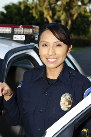 police badge: a smiling Hispanic police officer next to her patrol car.