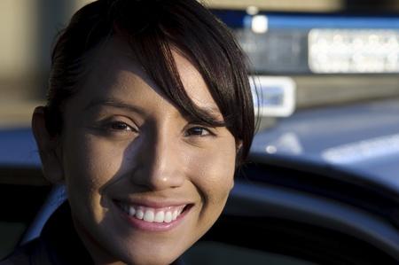 patrol cop: un oficial de polic�a de sexo femenino feliz de pie junto a su patrulla.