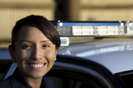 lightbar: a happy female police officer standing next to her patrol unit.  Stock Photo