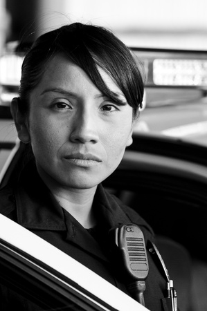 lightbar: a Hispanic female police officer looking serious while standing at her patrol car. Stock Photo