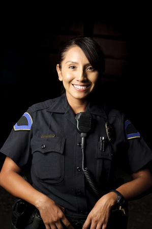 a smiling police officer posing for her portrait in the night.