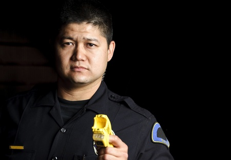 a male police officer pointing his taser gun at night.