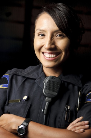 a female police officer smiling at night and posing for her portrait.  photo