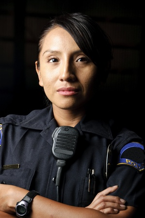 a female police officer posing for her portrait at night.  photo