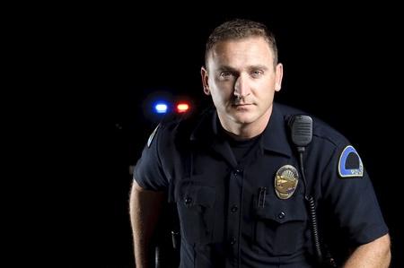 patrol cop: un oficial de polic�a de pie en la noche durante un turno de patrulla. Foto de archivo